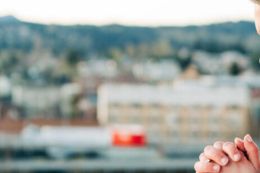 Woman praying with a city in the background, ready to change the world